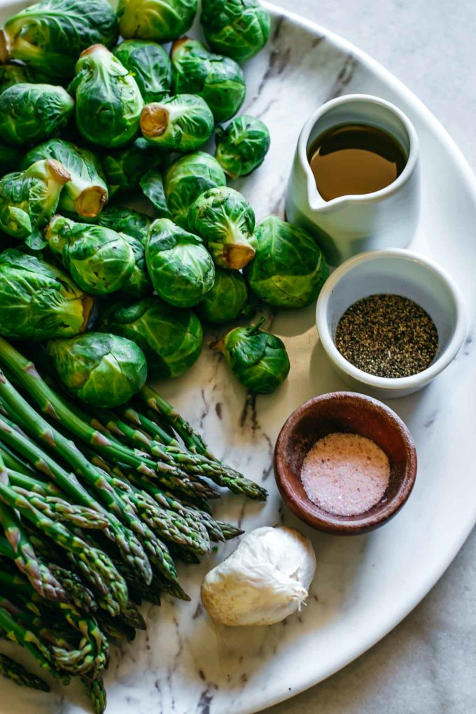 brussels sprouts, asparagus, garlic and bowls of olive oil, salt and pepper on a white table