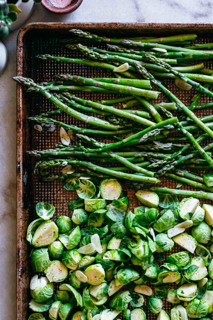 chopped raw brussels sprouts and asparagus arranged on a baking sheet