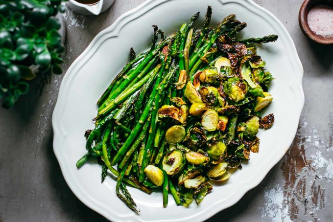 oven roasted asparagus and brussels sprouts on a white platter