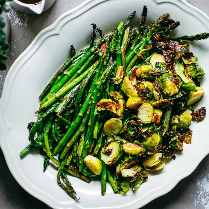 roasted brussels sprouts and asparagus on a white platter