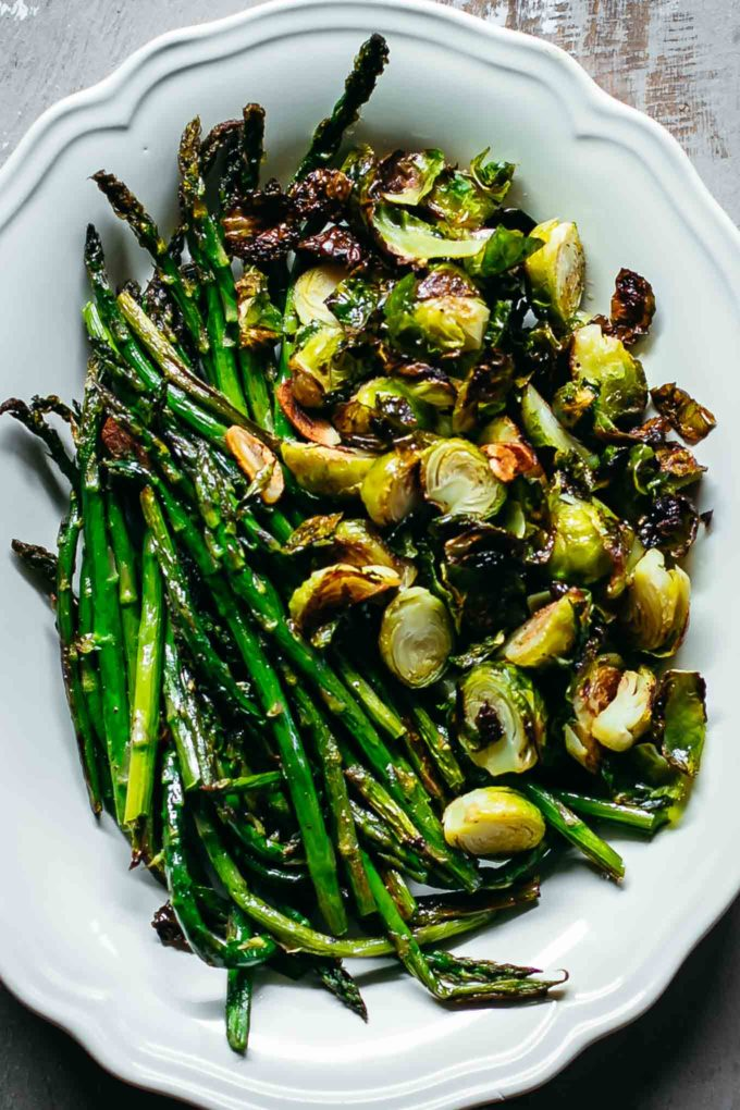 roasted asparagus and brussels sprouts in a white serving dish