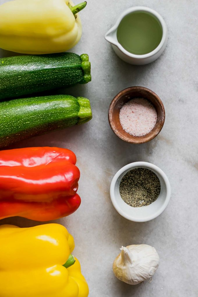 zucchini, bell peppers, and bowls of olive oil, salt, and pepper on a white table