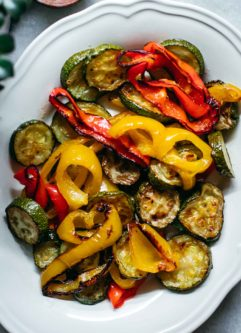 baked bell peppers and zucchini on a white plate