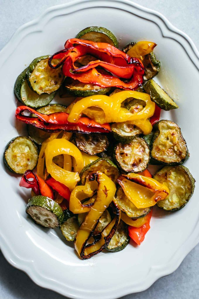 roasted zucchini and peppers on a white plate on a white countertop