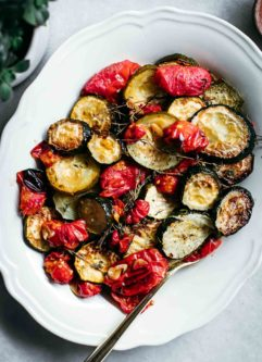 roasted tomatoes and zucchini on a white serving plate