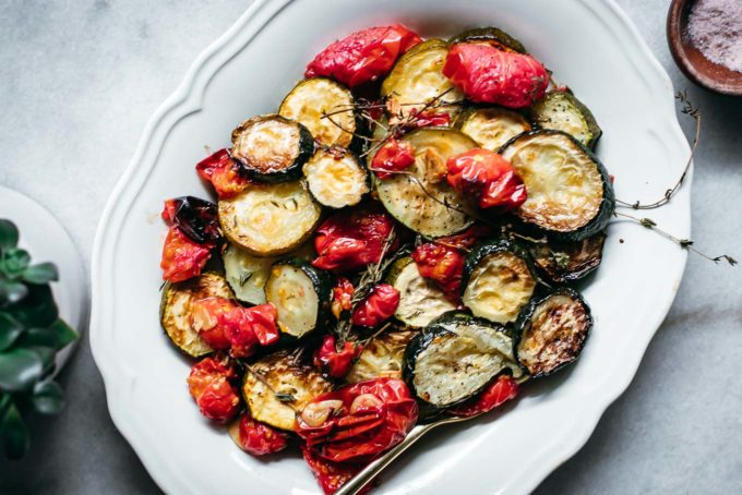 baked tomatoes and zucchini on a white plate