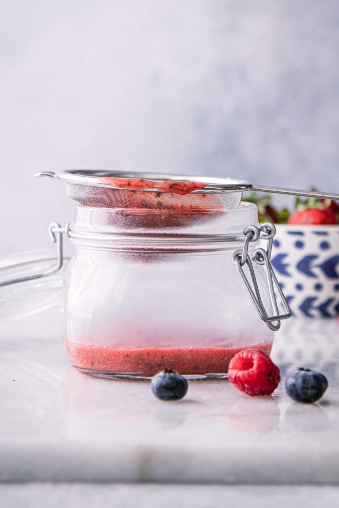 a mesh strainer with strawberry puree over a glass bowl on a white table
