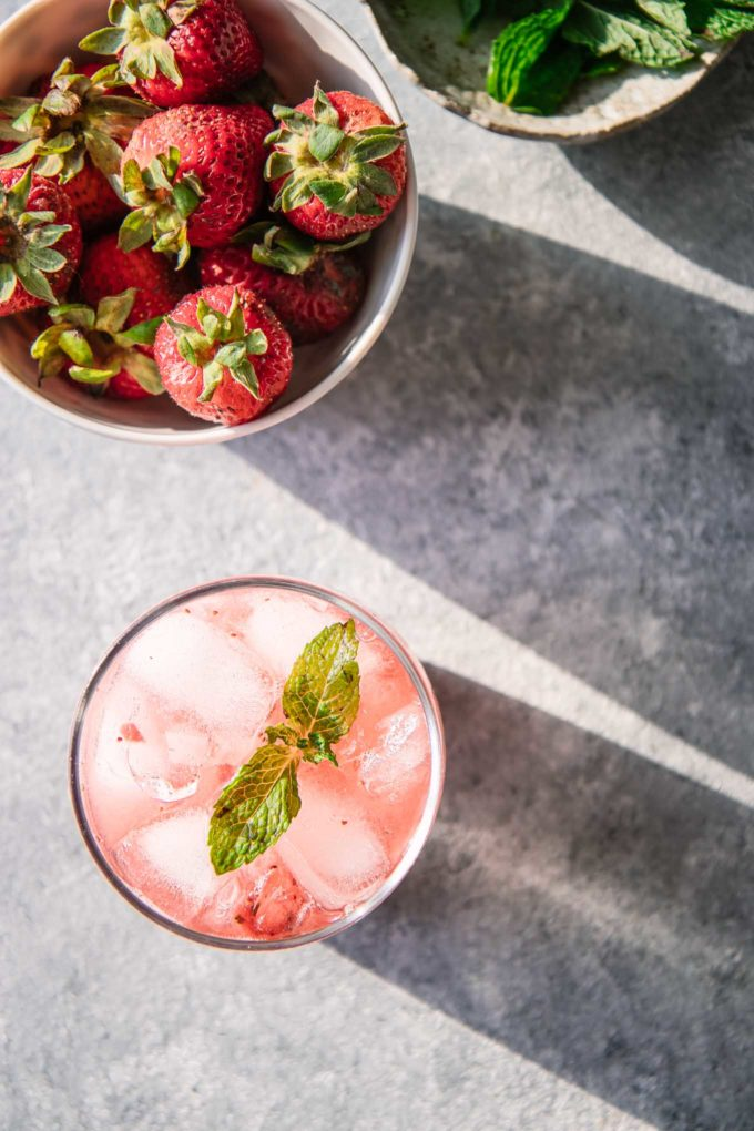 a pink mocktail on a table with a bowl of strawberries and mint