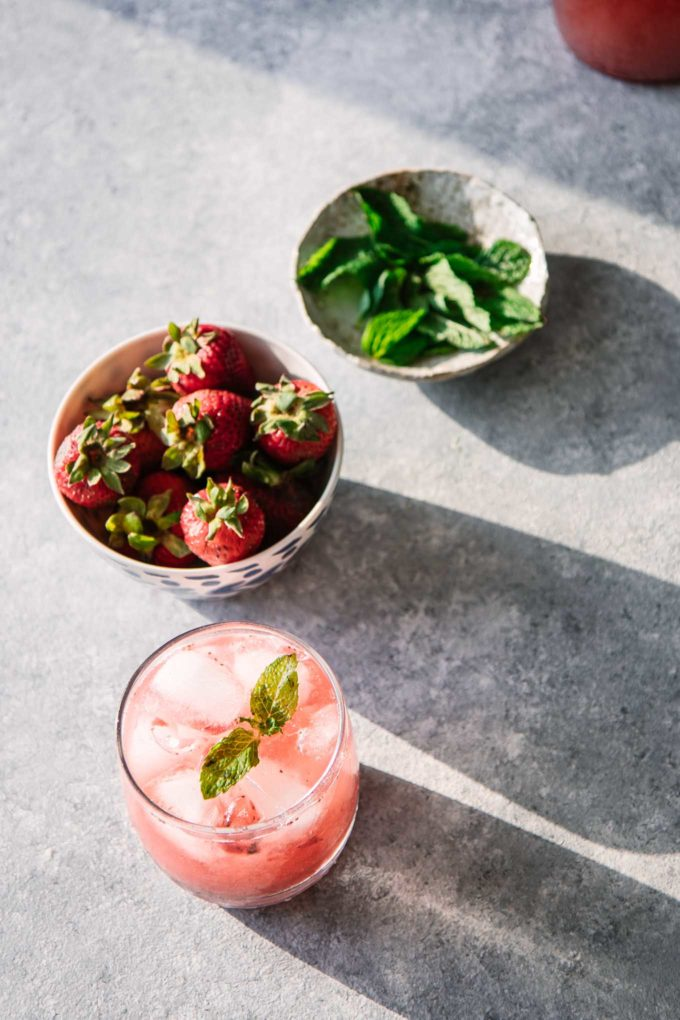 strawberries, mint, and a water spritzer on a blue table