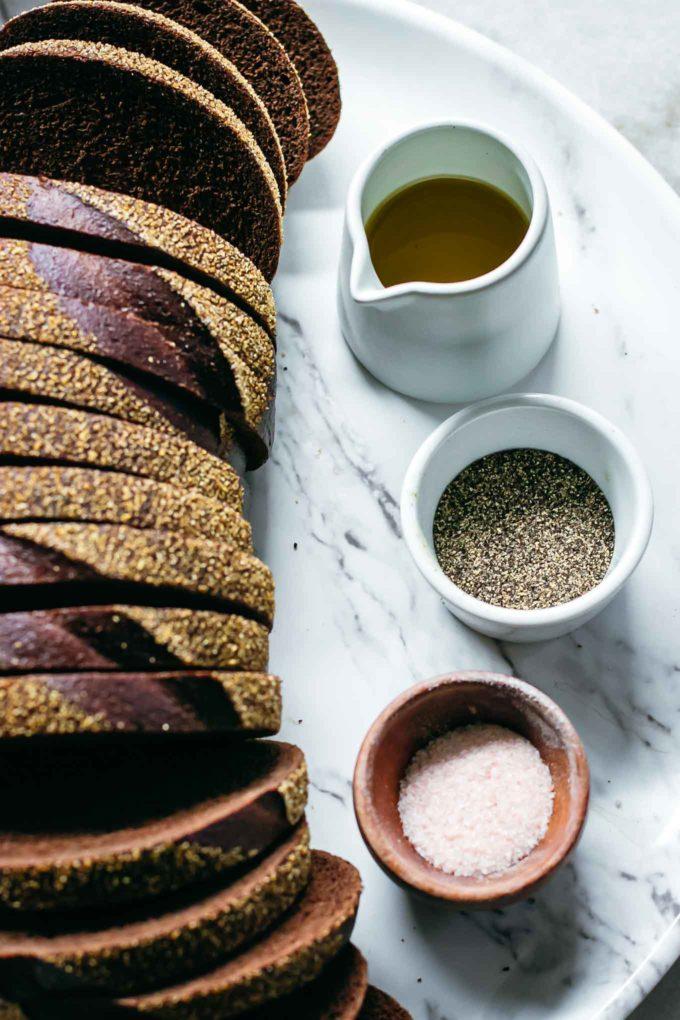 sliced loaf of pumpernickel bread, olive oil, salt and pepper on a white table