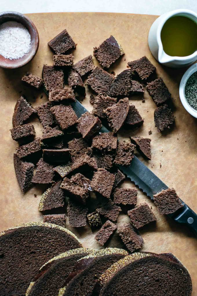 slices and cubes of pumpernickel bread on a cutting board with a serrated knife