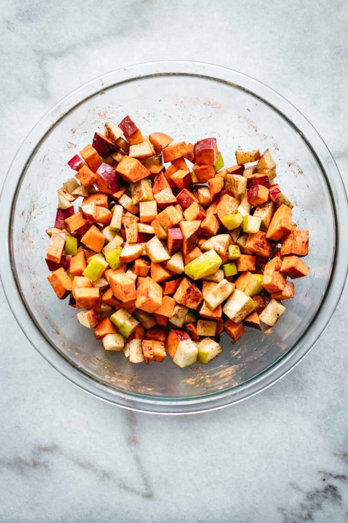 diced sweet potatoes and apples in a glass bowl with cinnamon and salt