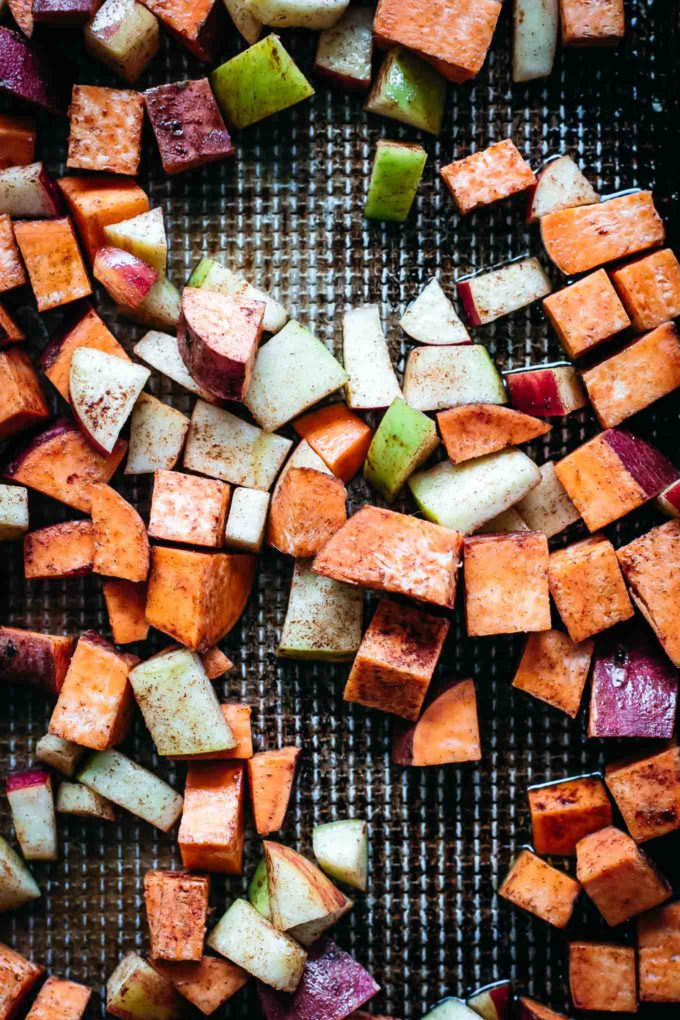 cubed sweet potatoes and apples on a roasting pan before baking