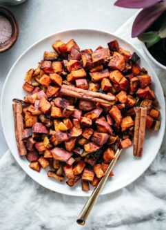roasted diced sweet potatoes and apples on a white plate with cinnamon sticks