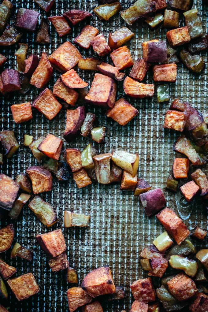 cooked sweet potatoes and apples on a baking sheet