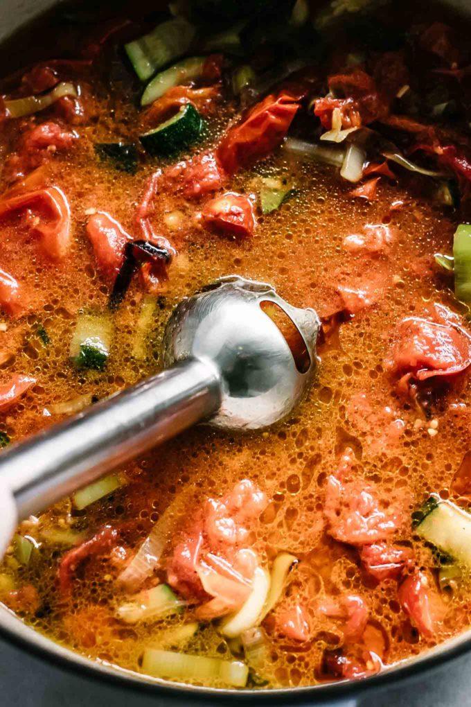 an immersion blender inside a pot of tomato soup