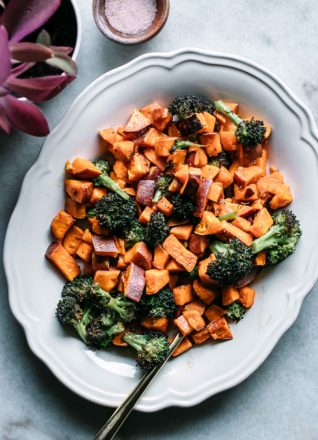 baked broccoli and sweet potatoes on a plate with a gold fork